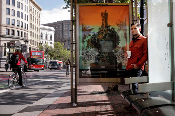 "Robert Minervini stands at a bus stop displaying his artwork ""Le Poème de la Vigne (With Wine Grapes)."""