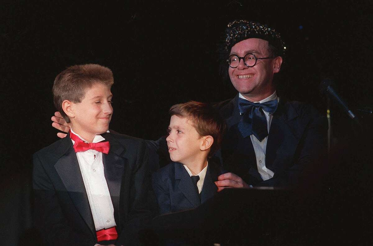 """Singer Elton John is joined by Ryan White, left, and Jason Robertson, both suffering from AIDS July 9, 1988 as he performs at """"For The Love of Children,"""" a benefit for children with AIDS, and other serious illnesses or problems, at the Century Plaza Hotel in Los Angeles, July 9, 1988. John appeared on stage for the first time in two years. (AP Photo/Alan Greth)"""