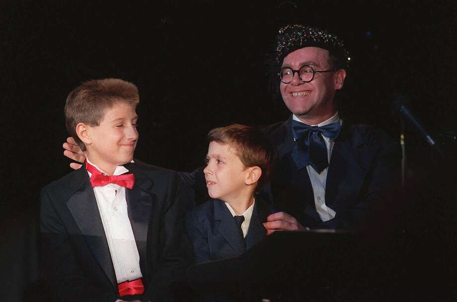 "Singer Elton John is joined by Ryan White, left, and Jason Robertson, both suffering from AIDS July 9, 1988 as he performs at ""For The Love of Children,"" a benefit for children with AIDS, and other serious illnesses or problems, at the Century Plaza Hotel in Los Angeles, July 9, 1988.  John appeared on  stage for the first time in two years. (AP Photo/Alan Greth) Photo: Ap, AP"