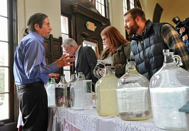Trent Millet, left, talks to Jared Rifenbary of Saratoga Springs, right, as he pours different kinds of water after Saratoga Springs Mayor Joanne Yepsen and the City Centennial Committee Marked the 100th Anniversary of the April 7, 1915 Incorporation of the City of Saratoga Springs at the Saratoga Springs Visitors Center on Tuesday, April 7, 2015 in Saratoga Springs, N.Y.  (Lori Van Buren / Times Union) Photo: Lori Van Buren / 00031325A