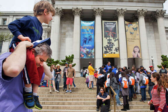 Chris Cellini of Charlotte, N.C., left, lifts his son Aiden Cellini, 5, onto his shoulders after a visit to the Natural History Museum on the National Mall in Washington, Tuesday, April 7, 2015. Widespread power outages affected the White House, State Department, Capitol and other sites across Washington and its suburbs Tuesday afternoon — all because of an explosion at a power plant in southern Maryland, an official said.
