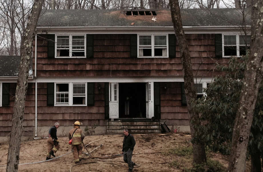 Firefighters cut a hole in the roof of a home that caught fire Tuesday, April 7, 2015, in Stamford, Conn. The 94-year-old homeowner escaped unharmed. Photo: John Nickerson / Stamford Advocate