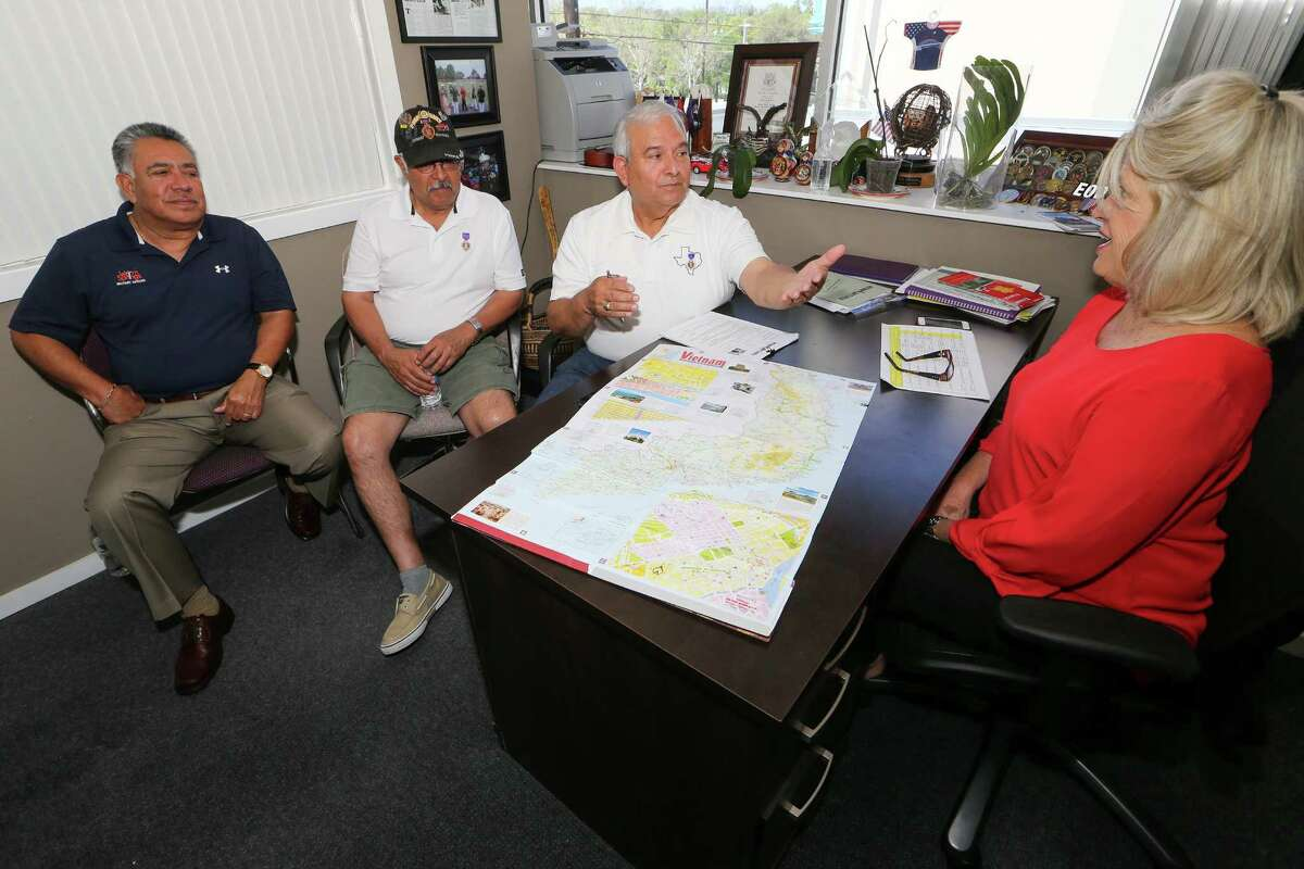 Tony Fuentes (from left), Lorenzo Rodriguez and Manuel Soto talk about their recent trip back to Vietnam with Janice Roznowski of Operation Comfort.