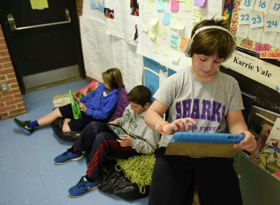 Fifth grader Robert Rota, right, uses the eSpark iPad app beside classmates Arto Stepanian, left, and Louis Ceci at Parkway School in Greenwich, Conn. Thursday, March 26, 2015.  Parkway is the only school in the Greenwich district to use eSpark, a personalized iPad app for students that curates a variety of education applications for students to use supplemental to standard lessons.  Through apps, videos and assessments, eSpark gives students personalized learning programs and lets teachers give students more customized feedback. Photo: Tyler Sizemore / Greenwich Time