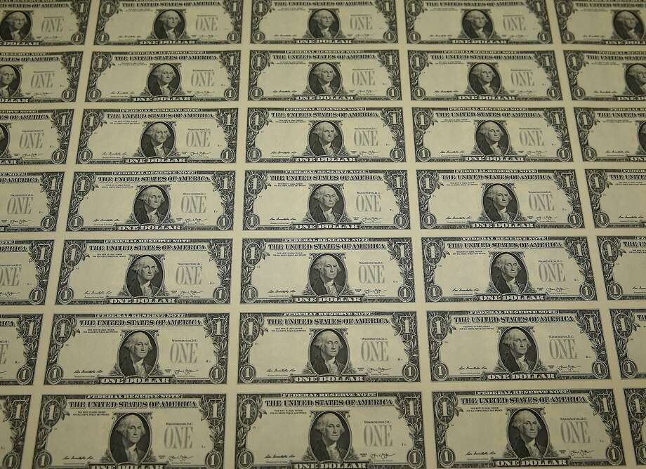WASHINGTON, DC - MARCH 24: A sheet of freshly printed one dollar bills is ready for inspection at the Bureau of Engraving and Printing on March 24, 2015  in Washington, DC. The roots of The Bureau of Engraving and Printing can be traced back to 1862, when a single room was used in the basement of the main Treasury building before moving to its current location on 14th Street in 1864. The Washington printing facility has been responsible for printing all of the paper Federal Reserve notes up until 1991 when it shared the printing responsibilities with a new western facility that opened in Fort Worth, Texas.  (Photo by Mark Wilson/Getty Images) Photo: Mark Wilson, Getty Images