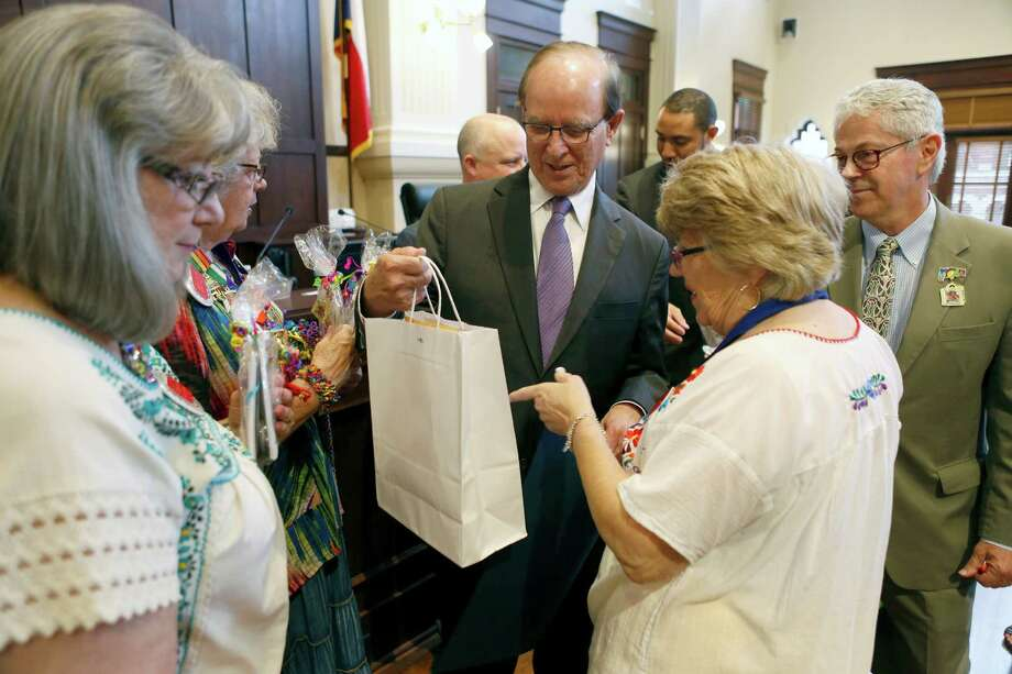 County Judge Nelson Wolff receives a small gift bag April 7 from members of the San Anotnio Conservation Society during the ceremonial portion of the Bexar County Commissioners Court. The commissioners read several Fiesta-related proclamations including one recognizing the conservation society for its work developing A Night in Old San Antonio. Photo: William Luther /San Antonio Express-News / © 2015 San Antonio Express-News