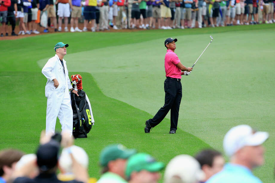 Tiger Woods hits a shot as caddie Joe LaCava watches during a practice round prior to the start of the Masters at Augusta (Ga.) National Golf Club.  On Wednesday, Woods will play in the event's family-friendly Par-3 contest for the first time since 2004. Photo: Jamie Squire / Getty Images / 2015 Getty Images