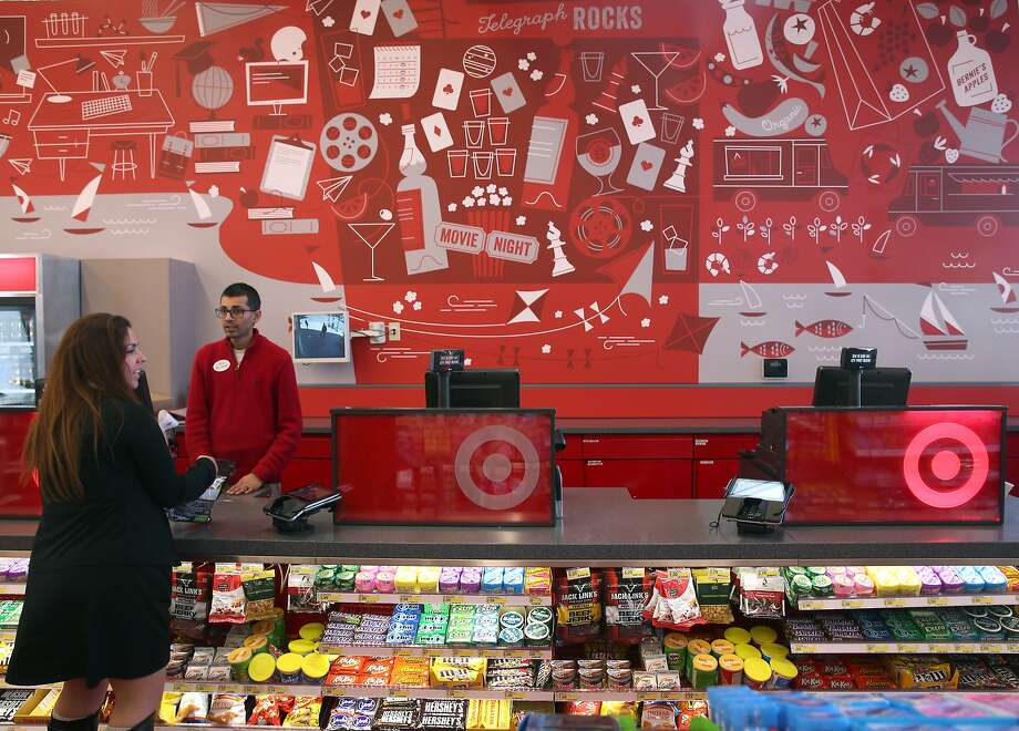 Store manageer Chintan Maniar assists a customer below a mural by local artist Eszter Clark at the Target Express store in Berkeley, Calif. on Tuesday, April 7, 2015. The Minneapolis-based big box retailer opened the smaller store near the Cal campus which caters to the university community and is the third such store that Target has opened nationally. Photo: Paul Chinn, The Chronicle