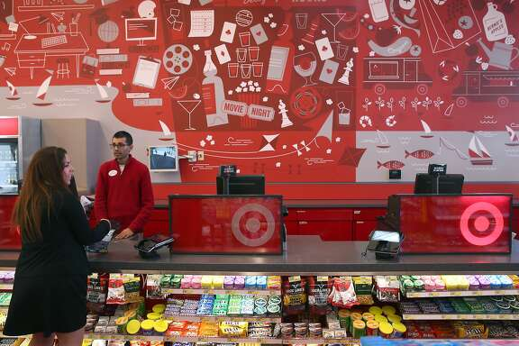 Store manageer Chintan Maniar assists a customer below a mural by local artist Eszter Clark at the Target Express store in Berkeley, Calif. on Tuesday, April 7, 2015. The Minneapolis-based big box retailer opened the smaller store near the Cal campus which caters to the university community and is the third such store that Target has opened nationally.