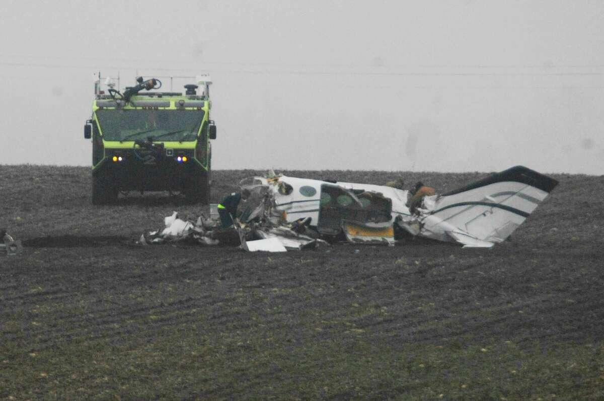 A coroner pronounced all seven occupants of the small private plane dead at the crash site in a field near Bloomington, Ill.