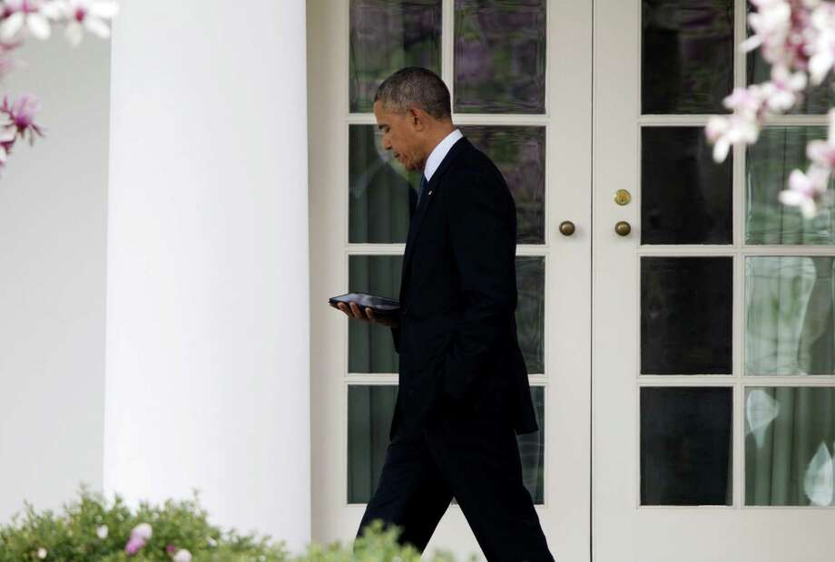 President Barack Obama reads as he walks back to the Oval Office of the White House in Washington, Tuesday, April 7, 2015, before traveling to Howard University to discuss climate change. (AP Photo/Pablo Martinez Monsivais) Photo: Pablo Martinez Monsivais, STF / AP