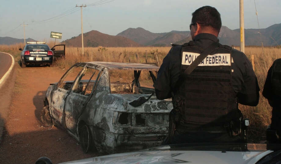 Federal police stand next to a burned car after gunmen ambushed a police convoy in Jalisco state. Photo: Associated Press / AP
