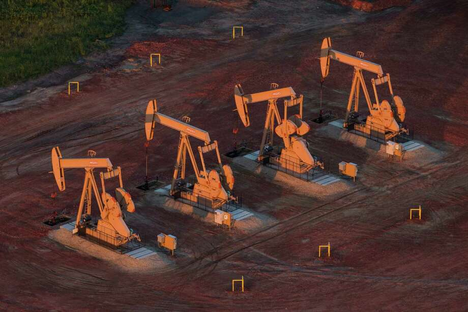 Pumpjacks bring up oil from wells in North Dakota. U.S. crude prices rose Tuesday after a government report projected the nation's surging production would level off later this year.  (Photo by Andrew Burton/Getty Images) Photo: Andrew Burton, Staff / 2013 Getty Images