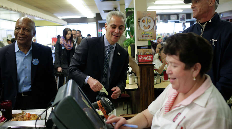 Mayor Rahm Emanuel (center) jokes with the cashier at Manny's Deli as he waits in line for a receipt. Photo: Joshua Lott / 2015 Getty Images