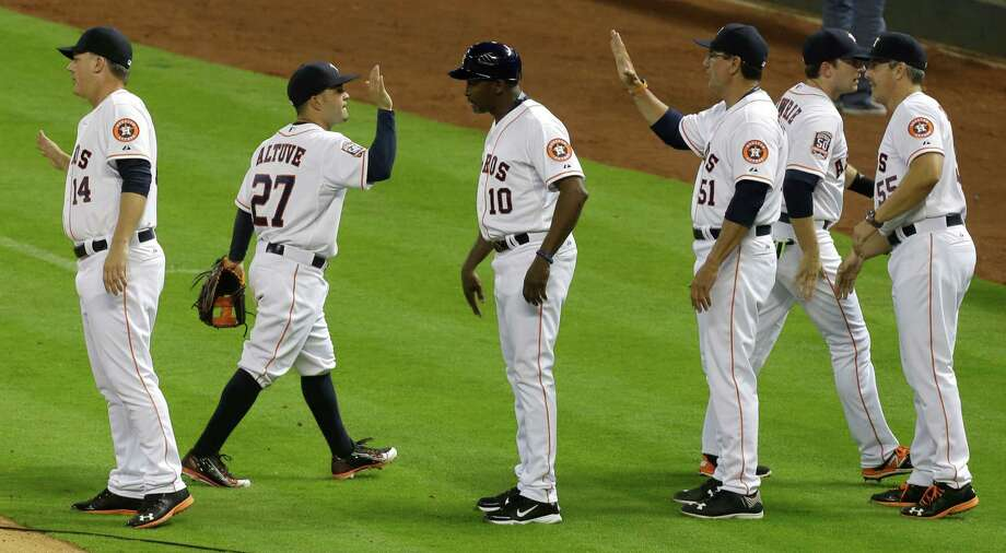 A.J. Hinch, left, hits the field to greet his triumphant team, including Jose Altuve (27), after a perform-ance Monday in which the execution by the new manager and his players was virtually mistake-free. Photo: Melissa Phillip, Staff / © 2015  Houston Chronicle