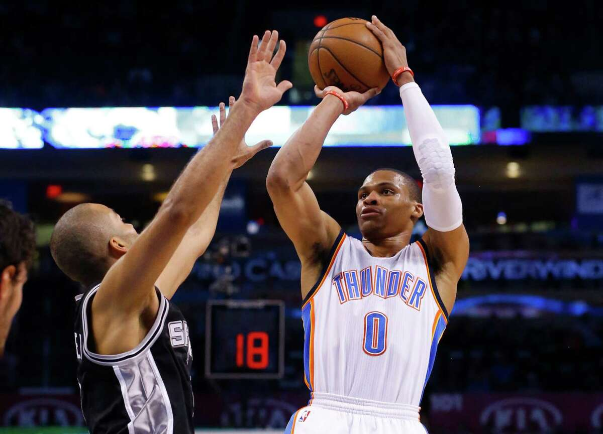 Oklahoma City Thunder guard Russell Westbrook (0) shoots over San Antonio Spurs guard Tony Parker during the first quarter of an NBA basketball game in Oklahoma City, Tuesday, April 7, 2015.