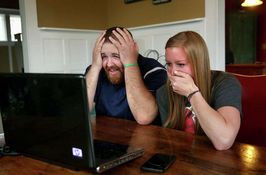 In this Monday, April 6, 2015 photo, Joel Burger and Ashley King react at King's home in New Berlin, Ill., after learning from a New York public relations firm that Burger King has offered to pay the expenses and provide gifts for their wedding because of their interesting connection to the fast food restaurant chain. The State Journal-Register reports that the couple has been known as Burger-King since they were in the fifth grade together, in New Berlin near Springfield. The Burger-King nuptials will be held July 17 in Jacksonville, Ill. (AP Photo/The State Journal-Register, David Spencer)  NO SALES Photo: David Spencer, MBR / The State Journal-Register