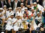 This June 15, 2014 file photo shows the San Antonio Spurs as they celebrate with the Larry O'Brien NBA Championship Trophy after the Spurs defeated the Miami Heat 107-84 in Game 5 of the NBA Finals to win the NBA Finals Championship, in San Antonio,Texas.  Front row from left: MVP Kawhi Leonard, Tony Parker, Tim Duncan, Manu Ginobili and Patty Mills.  The NBA's defining moment in 2014 was supposed to be the San Antonio Spurs return to championship glory, but that was before the Donald Sterling saga took on a life of its own. With the perfect blend of youth and experience, the Spurs dismantled the Miami Heat in one of the most lop-sided finals in league history, showing the two-time defending champions that the secret to long-term success is strong leadership and developing young talent. Future hall of famers Tim Duncan, Tony Parker and Manu Ginobili teamed up to lead the Spurs past the Heat in five games. For France's Parker and Argentina's Ginobili it was their fourth ring with the Spurs. For the Virgin Islands-born Duncan and coach Gregg Popovich it marked five rings together. AFP PHOTO / Robyn BeckROBYN BECK/AFP/Getty Images