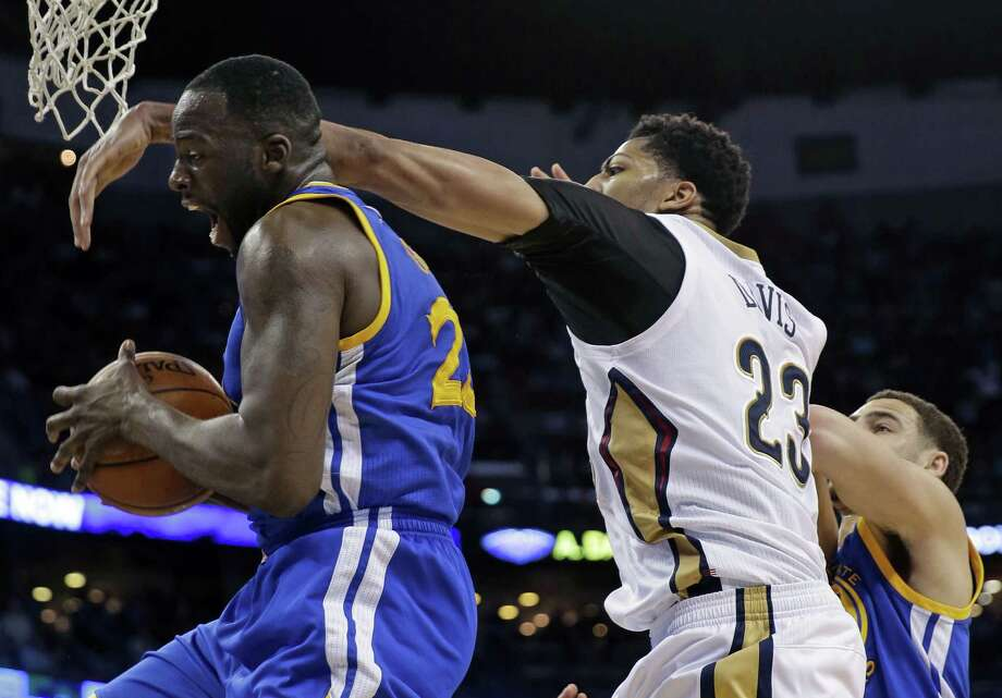 Warriors forward Draymond Green, left, battles the Pelicans' Anthony Davis during Tuesday night's crucial Western Conference game. Photo: Gerald Herbert, STF / AP