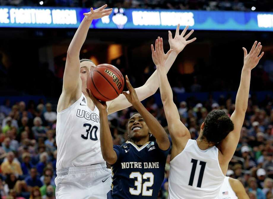 TAMPA, FL - APRIL 07:  Jewell Loyd #32 of the Notre Dame Fighting Irish goes up for a basket as Breanna Stewart #30 and Kia Nurse #11 of the Connecticut Huskies defend during the NCAA Women's Final Four National Championship at Amalie Arena on April 7, 2015 in Tampa, Florida.  (Photo by Mike Carlson/Getty Images) Photo: Mike Carlson, Stringer / 2015 Getty Images