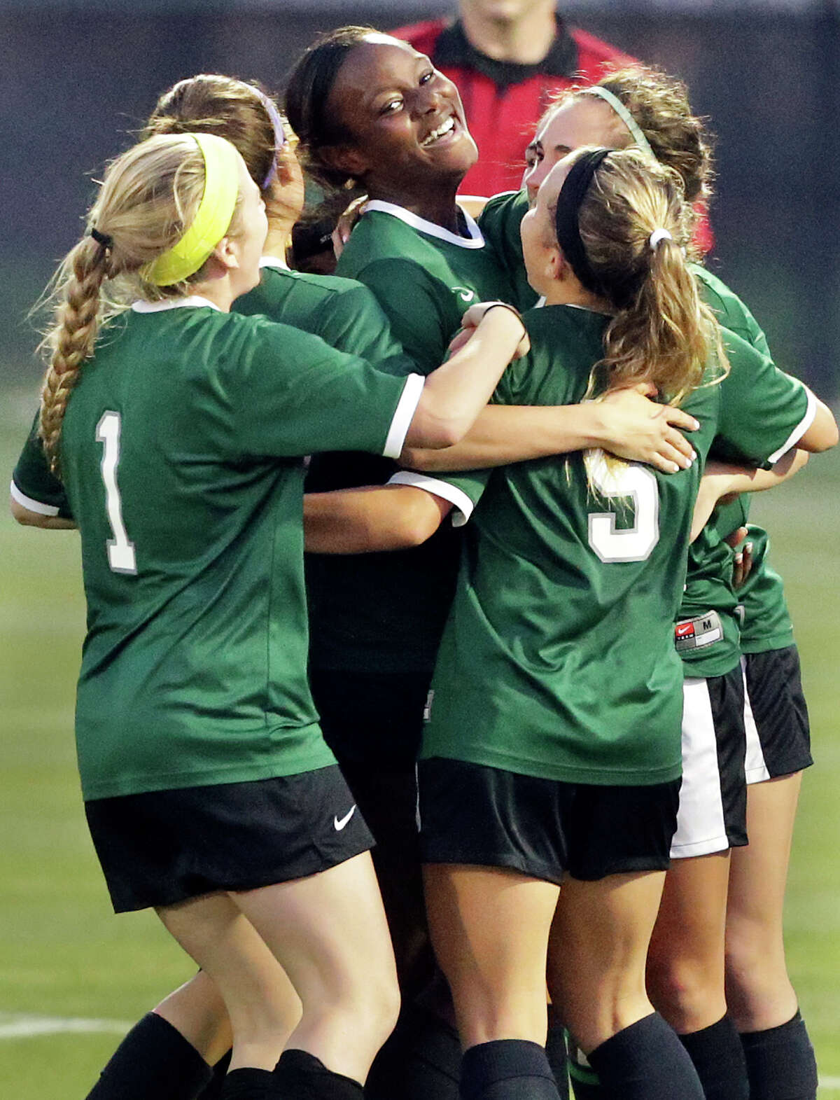 Teammates congratulate Tia Pearcy on her goal which proved to be the winning score as the Reagan girls beat Smithson Valley 1-0 in third round 6A soccer playoffs at the UTSA Park West Complex on April 7, 2015.