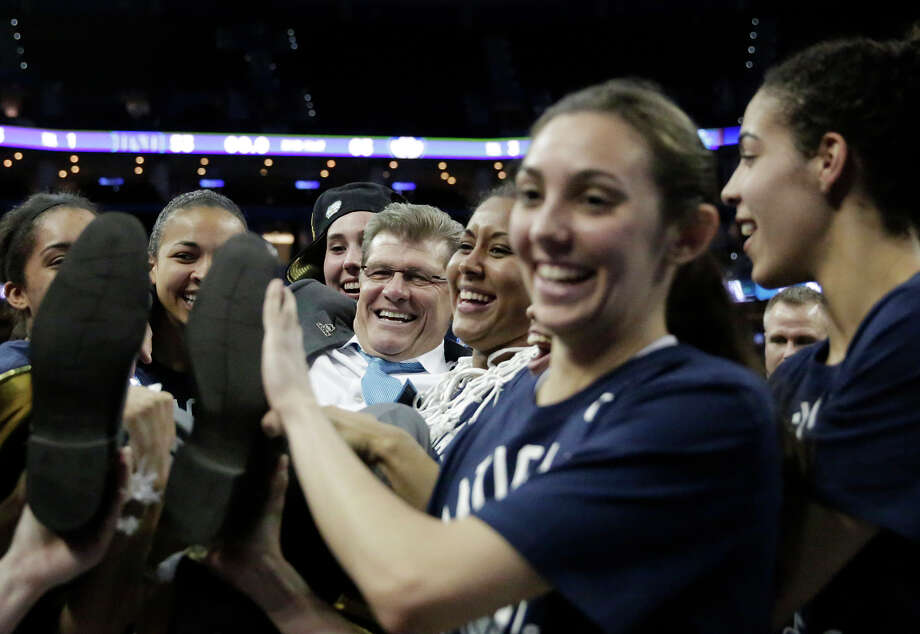 The Connecticut players carry Geno Auriemma (center) off the court after winning their third straight national title and Auriemma's 10th as head coach. Photo: Brynn Anderson / Associated Press / AP