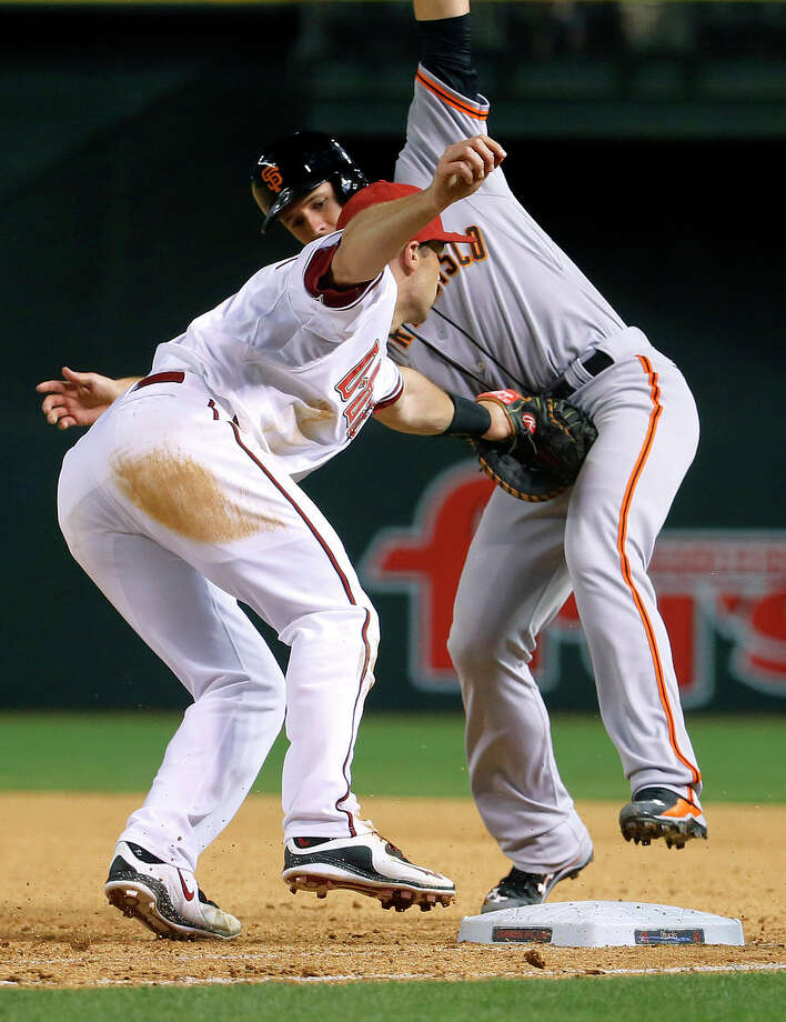 Arizona first baseman Paul Goldschmidt tags out the Giants' Buster Posey on a pickoff during the seventh inning. Photo: Matt York / Associated Press / AP