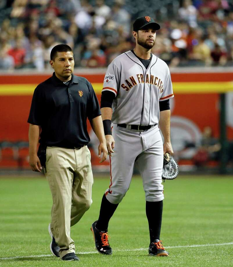 San Francisco Giants first baseman Brandon Belt leaves the game with  the trainer during the fourth inning of a MLB baseball game against the Arizona Diamondbacks, Tuesday, April 7, 2015, in Phoenix. (AP Photo/Matt York) Photo: Matt York / Associated Press / AP