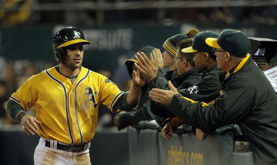 Sam Fuld (23) is high fived after scoring the A's only run in the sixth inning as the Oakland Athletics played the Texas Rangers at O.Co Coliseum on Tuesday, April 7, 2015, in Oakland, Calif. Photo: Carlos Avila Gonzalez, The Chronicle