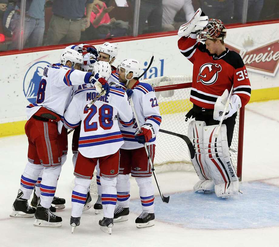 The Rangers celebrate after James Sheppard (45) scored a goal on Devils goalie Cory Schneider (right) during the third period. The win clinched the Presidents' Trophy for New York. Photo: Julio Cortez / Associated Press / AP