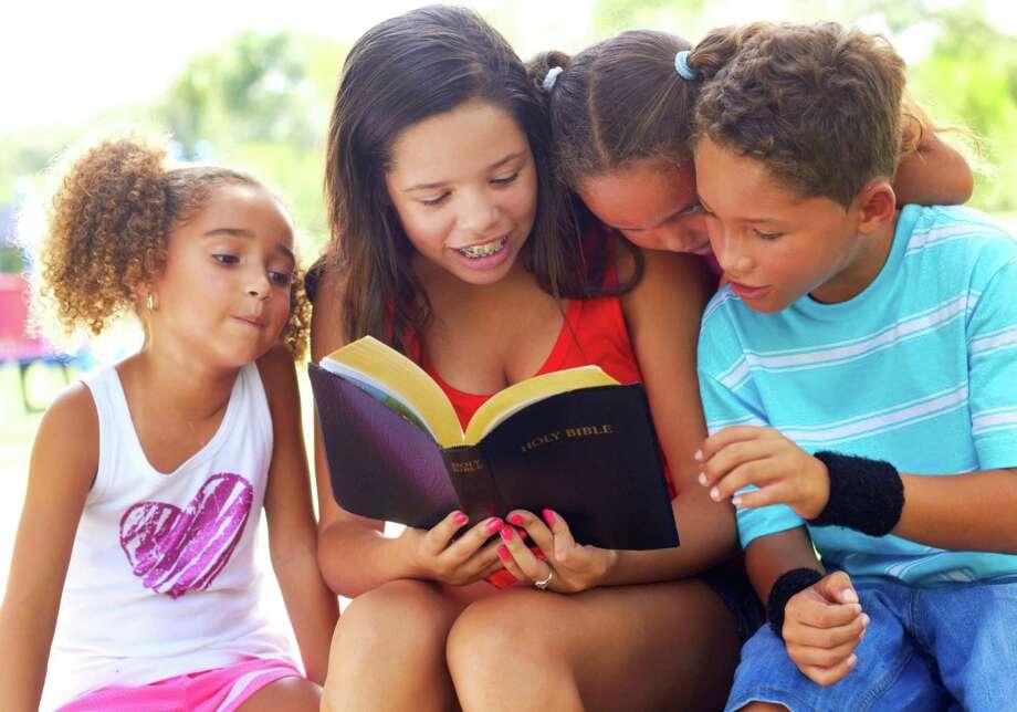 Teenage Girl Reading Bible To Siblings At Park Photo: Matthewennisphotography / iStockphoto