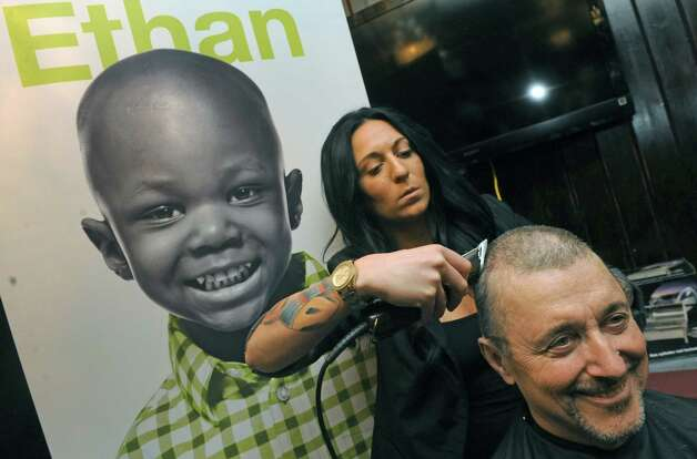 Albany County Comptroller Mike Conners gets his head shaved by Kayla Pelton Of Barber Bettys at McGeary's Pub on Tuesday April 7, 2015 in Albany, N.Y. Mike Conners let donors shave his hair off for charity before he loses it to chemotherapy. The proceeds will go to the St. Jude Children's Hospital and three others battling illness. (Michael P. Farrell/Times Union) Photo: Michael P. Farrell / 00031331A