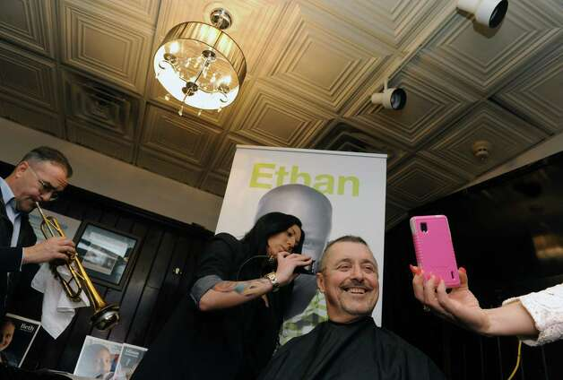 "Albany County Comptroller Mike Conners gets his head shaved by Kayla Pelton Of Barber Betty's at McGeary's Pub on Tuesday April 7, 2015 in Albany, N.Y. Mike Conners let donors shave his hair off for charity before he loses it to chemotherapy. The proceeds will go to the St. Jude ChildrenOs Hospital and three others battling illness. Trumpeter Don Arnold, left, played the song ""I'm Just Wild About Harry"" during the clipping. (Michael P. Farrell/Times Union) Photo: Michael P. Farrell / 00031331A"