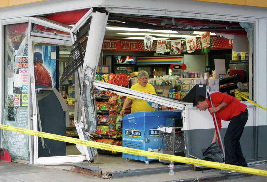 Carolina Estrada, left, and Hector Dehoyos, right, clean up after a smash-and-grab, at a Shell gas station along Hollister near the Northwest Freeway, Wednesday, April 8, 2015, in Houston. Photo: Cody Duty, Houston Chronicle / © 2015 Houston Chronicle