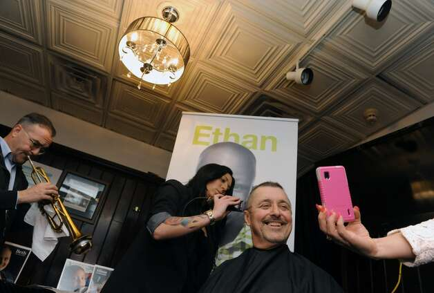 "Albany County Comptroller Mike Conners gets his head shaved by Kayla Pelton Of Barber Betty's at McGeary's Pub on Tuesday April 7, 2015 in Albany, N.Y. Mike Conners let donors shave his hair off for charity before he loses it to chemotherapy. The proceeds will go to the St. Jude ChildrenÕs Hospital and three others battling illness. Trumpeter Don Arnold, left, played the song ""I'm Just Wild About Harry"" during the clipping. (Michael P. Farrell/Times Union) Photo: Michael P. Farrell, Albany Times Union"