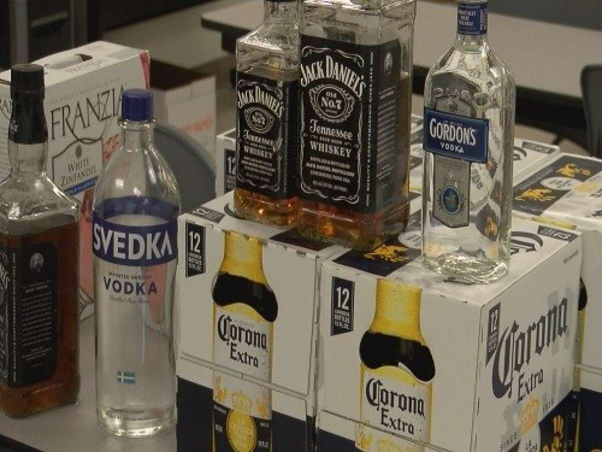 Seized alcohol is stacked on a table in front of Louisiana college students arrested April 6, 2015, in Mobile County, Ala., on citations for alleged underage drinking.