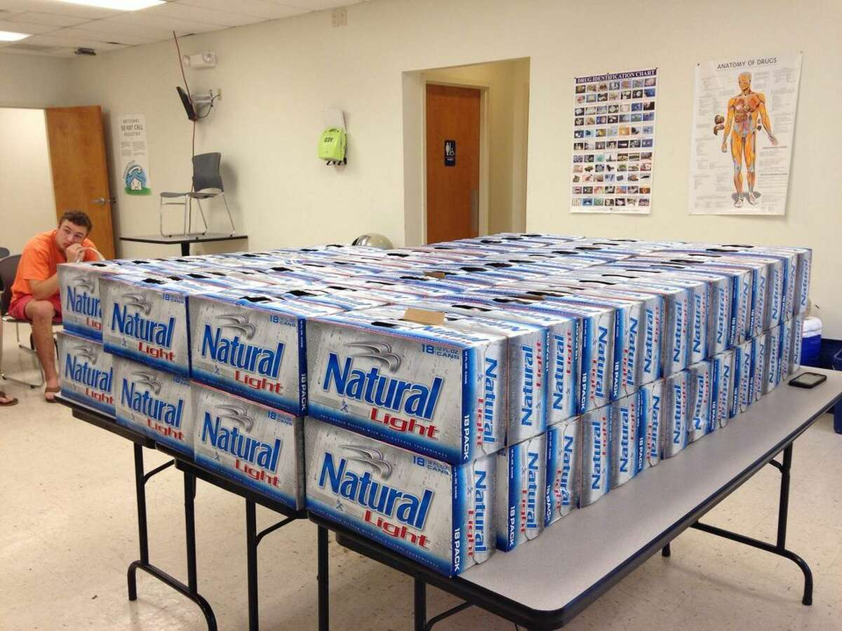 More than 100 cases of seized beer is stacked on a table in front of Louisiana college students arrested April 6, 2015, in Mobile County, Ala., on citations for alleged underage drinking. (Photo: Mobile County, Ala., Sheriff's Office)