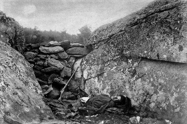 Slain rebel sharpshooter slumped down in his ineffective hideout, w. his rifle still perched against rocks, at end of Battle of Gettysburg during the Civil War.