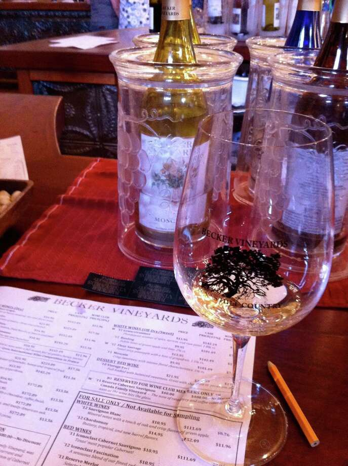 A souvenir glass and tasting menu are ready for the next sample in the Becker Vineyards tasting room near Stonewall. Photo: Terry Scott Bertling /San Antonio Express-News / San Antonio Express-News