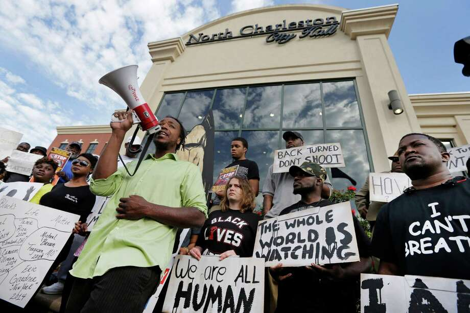 Muhiydin D'Baha leads a group protesting the shooting death of Walter Scott at city hall in North Charleston, S.C., Wednesday, April 8, 2015. Scott was killed by a North Charleston police office after a traffic stop on Saturday. The officer, Michael Thomas Slager,  has been charged with murder. Photo: Chuck Burton, AP / AP