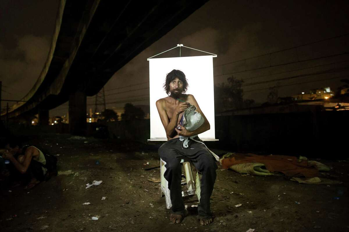 In this March 17, 2015 photo, Renato Dias, 39, writes in his notebook as he poses for a portrait in an open-air crack cocaine market, known as a