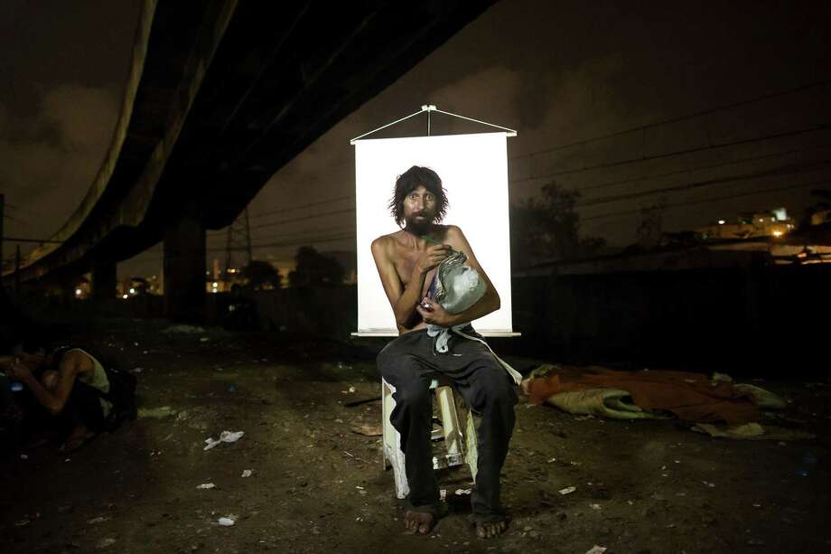 "In this March 17, 2015 photo, Renato Dias, 39, writes in his notebook as he poses for a portrait in an open-air crack cocaine market, known as a ""cracolandia"" or crackland, where users can buy crack, and smoke it in plain sight, day or night, in Rio de Janeiro, Brazil. Dias, who has been using crack for about 4 years, says he uses his notebook as a form of distraction. He writes about super heroes and dreams of becoming one. (AP Photo/Felipe Dana) Photo: Felipe Dana, Associated Press / AP"