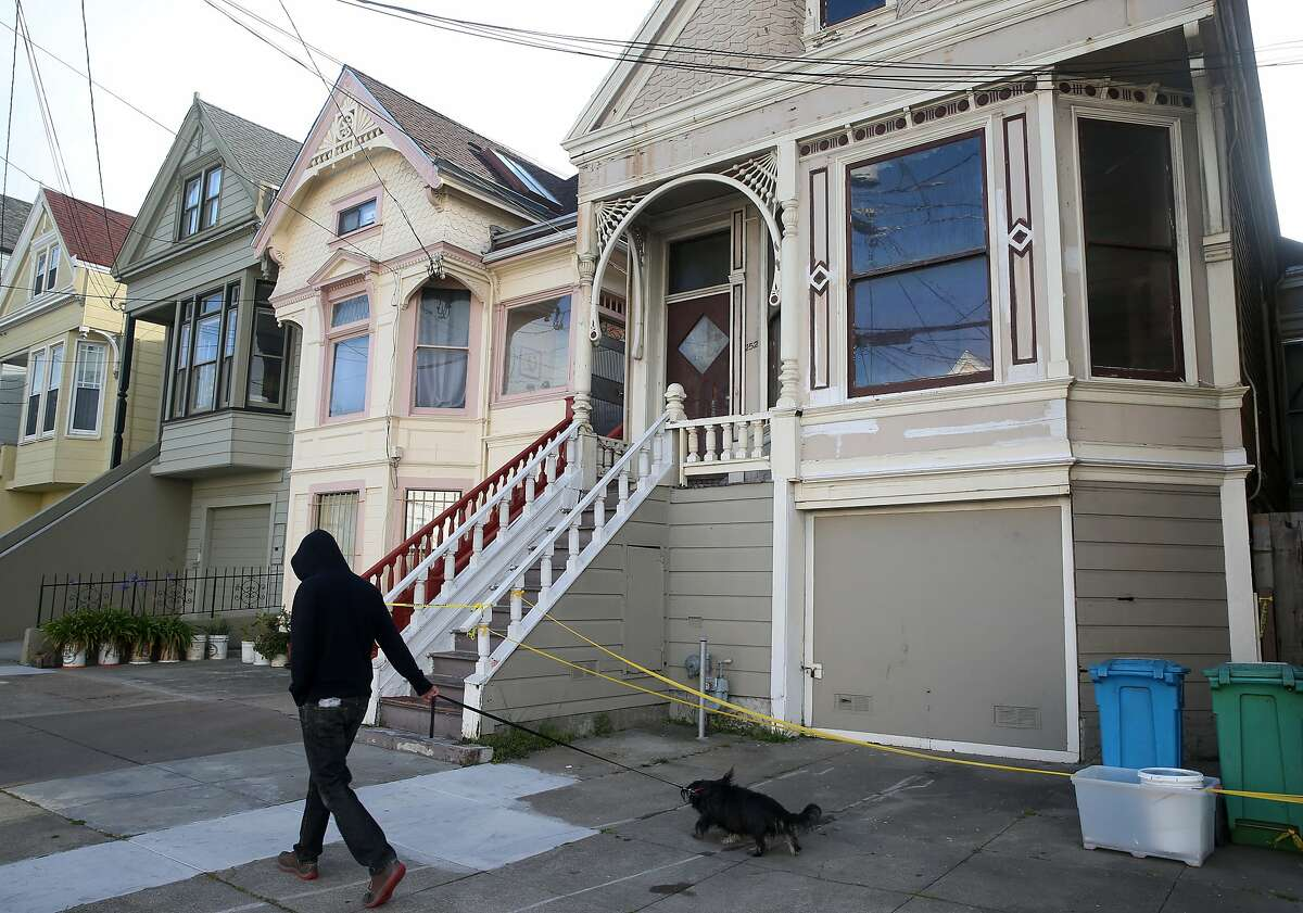 A neighbor walks his dog past a home on Fourth Avenue in San Francisco, Calif. on Wednesday, April 8, 2015, where a mummified body was removed over the weekend.