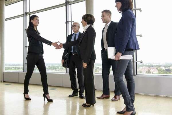 mature female boss with team, handshake
