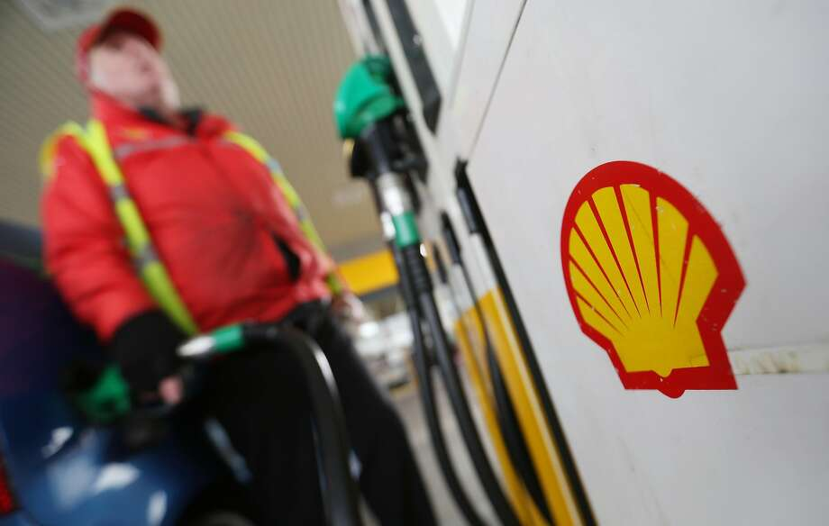 A fuel pump attendant stands on the forecourt of a gas station operated by Royal Dutch Shell Plc in Clacton-on-Sea, U.K., on Wednesday, April 8, 2015. Shell agreed to buy BG Group Plc for about 47 billion pounds ($70 billion) in cash and shares, the oil and gas industry's biggest deal in at least a decade. Photographer: Chris Ratcliffe/Bloomberg Photo: Chris Ratcliffe, Bloomberg