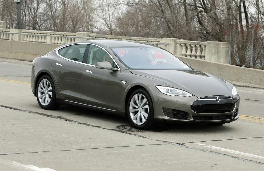 Tesla is introducing the Model S 70D, here on a test drive in Detroit. It has longer range and more power, and an instrument panel, below, displaying stats. Photo: Carlos Osorio / Associated Press / AP