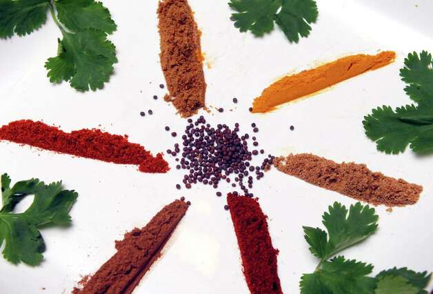Clockwise from top left, cumin, turmeric, coriander, paprika, cinnamon and cayenne with mustard seed in the center and garnished with cilantro all spices used in Indian cooking on Wednesday April 1, 2015 in Delmar, N.Y. (Michael P. Farrell/Times Union) Photo: Michael P. Farrell / 00031214A