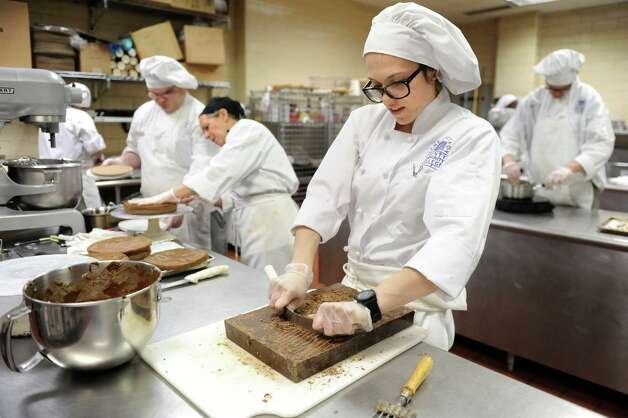 Culinary student Erica Brucculeri, 26, right, shaves chocolate in the baking lab on Tuesday, March 31, 2015, at Schenectady County Community College in Schenectady, N.Y. (Cindy Schultz / Times Union) Photo: Cindy Schultz / 00031237A