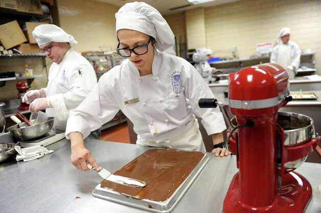 Culinary student Erica Brucculeri, 26, center, spreads a thin layer of chocolate in the baking lab on Tuesday, March 31, 2015, at Schenectady County Community College in Schenectady, N.Y. (Cindy Schultz / Times Union) Photo: Cindy Schultz / 00031237A