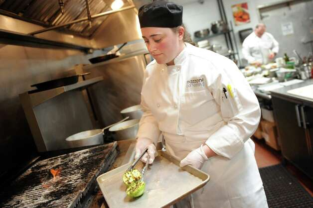 Culinary student Katie Brown, 23, sears an apple to garnish an appetizer platter on Tuesday, March 31, 2015, at Mazzone Hospitality Headquarters in Clifton Park, N.Y. Brown will graduate from Schenectady County Community College in May. (Cindy Schultz / Times Union) Photo: Cindy Schultz / 00031238A